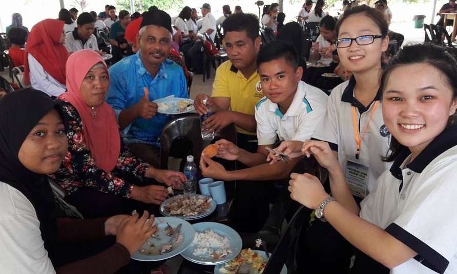 Two of the female trainees (right) enjoying fresh seafood with their foster family headed by Pacik Asim (with songkok).