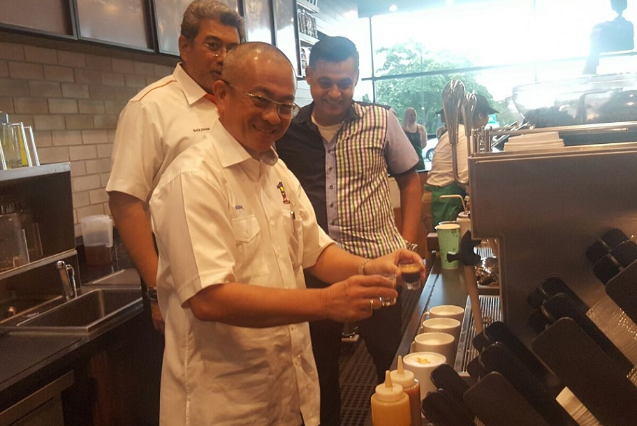 Labuan lawmaker, Datuk Rozman Isli, tries his hand at making a capucino, while Malaysia Airports managing director, Datuk Badlisham Ghazali Badlisham, left, and Starbuck's Quays, look on.