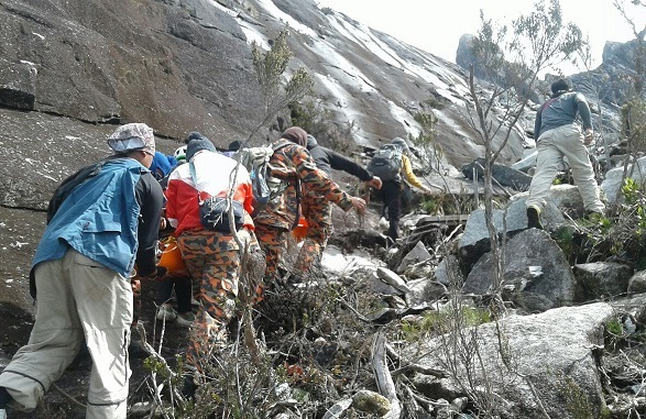 MOSAR personnel carrying down the remains of the Singapore endurance athlete who was found dead in a ravine on Mount Kinabalu Sunday