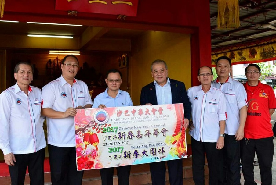 Goh (4th from right) presenting an invitation card for the Chinese New Year carnival to Chee (3rd from left), as several organising committee members look on.