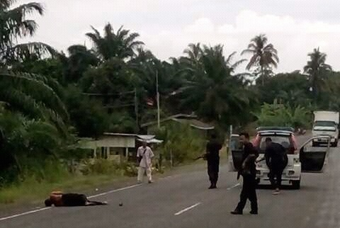 The body of the deceased lying by the roadside after he was shot dead by police.