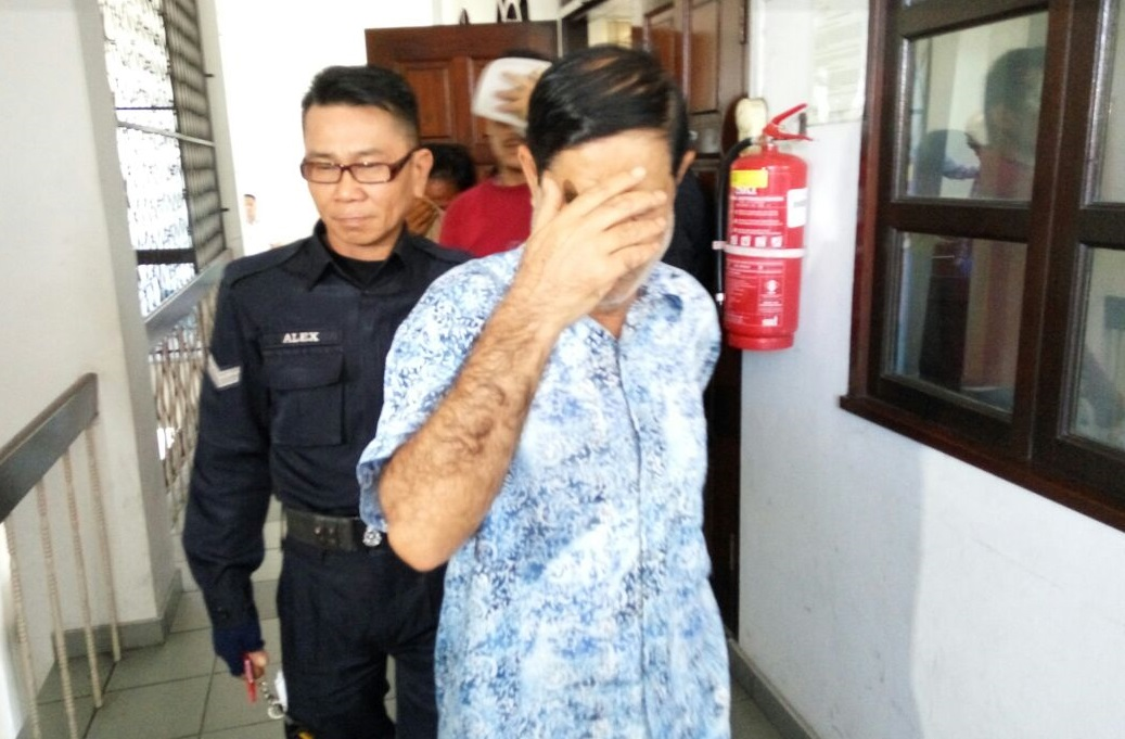 Salman Khan sheds his face from the cameras outside the court house in Kota Kinabalu on Wednesday.