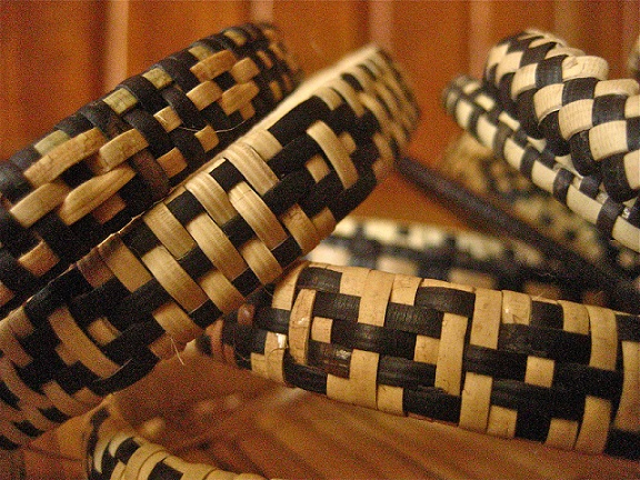 The handicraft is made from wild jungle rattan, stripped, smoothed and treated with the sap of a plant and buried overnight in mud for colouring. Then, carefully woven into intricate and meaningful designs.