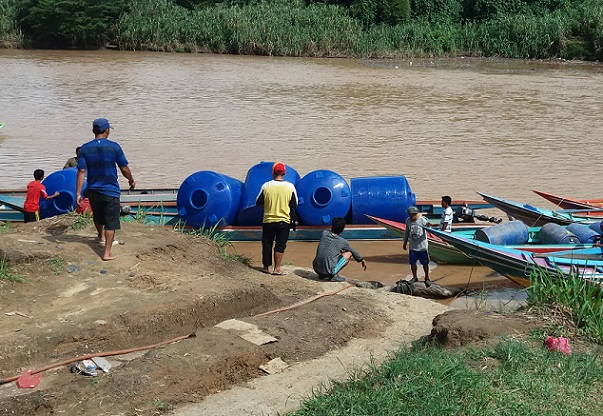 Elections soon. The blue tanks being transported to the jetty waiting to be boated down to long houses along the Sungai Loggongon. - Photos courtesy of Adrian Lasimbang