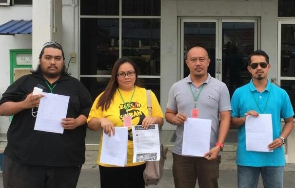 Beverly Joeman, second left, Mathhew Yong, second right and other Bersih Sabah members at the Karamunsing police station after lodging their reports against 'red-shirt' violence.