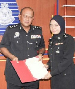 Inspector Haslinda Ahmad receiving the certificate of outstanding performance from Salehhuddin.