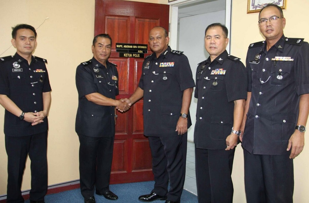 Sabah CID chief, Salehhuddin Abd Rahman, centre, congratulating Labuan police chief, Superintendent Adzhar Othman, second left, for his leadership qualities that enabled the island's police contingent achieve its key performance indicator (KPI).