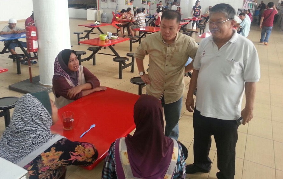 Accompanied by his assistant Teo Boon Ngee, standing at right, Chan listens to the complaints of hawkers at the Tawau UTC, concerning the bird droppings.