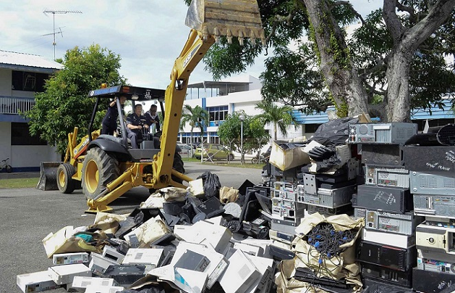 Labuan police chief Supt. Adzhar Othman behind the controls of an excavator, reducing to bits and pieces almost RM1 million worth of gaming machines after receiving the court order.