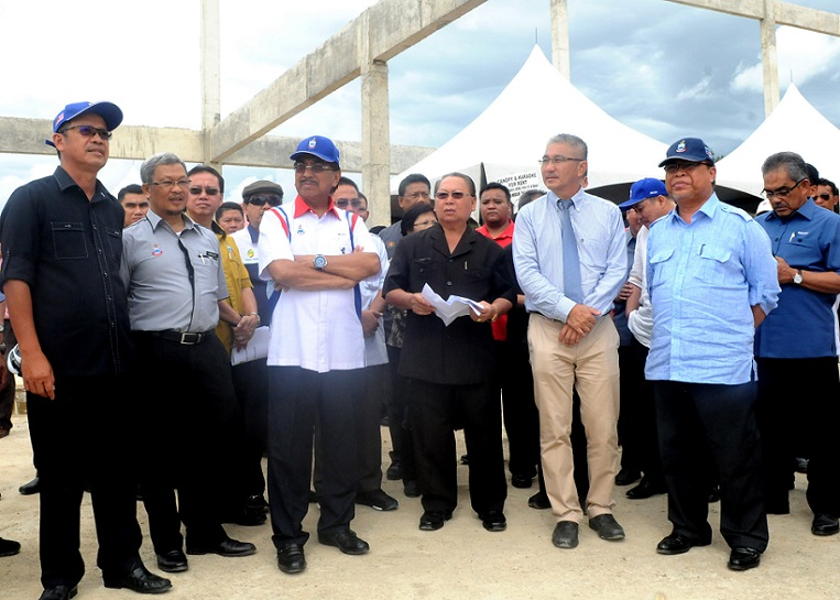 Ir.Edward Lingkapo, third from right, assistant director of the Public Works Department, briefs Musa, fourth left, and his entourage on the progress of the Beaufort sewerage works.