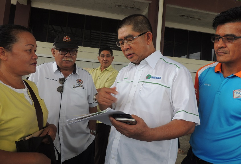 Ongkili, second right, talking to one of the villagers who came to the joint registration exercise held at Kota Marudu Community Hall, Friday. With him are Kota Kinabalu High Court Judge Datuk Douglas Primus, second left, and NRD's Abdon @ Nasir Ambikin (right).
