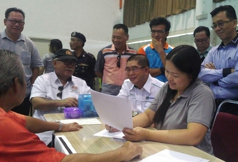Ongkili and Douglas overseeing the mobile registration exercise taking place at Kota Marudu Community Hall, watched by Abdon and other officers.