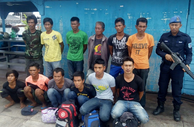 The 12 men who were detained in Pulau Denawan waters under armed guard and will be investigated for immigration offences.