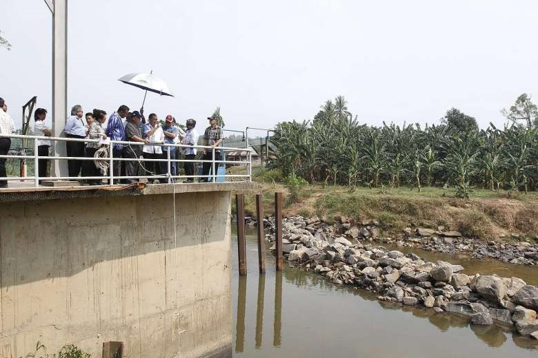 Pairin, in grey, and government officers visiting a water treatment plant in Penampang. - File photo