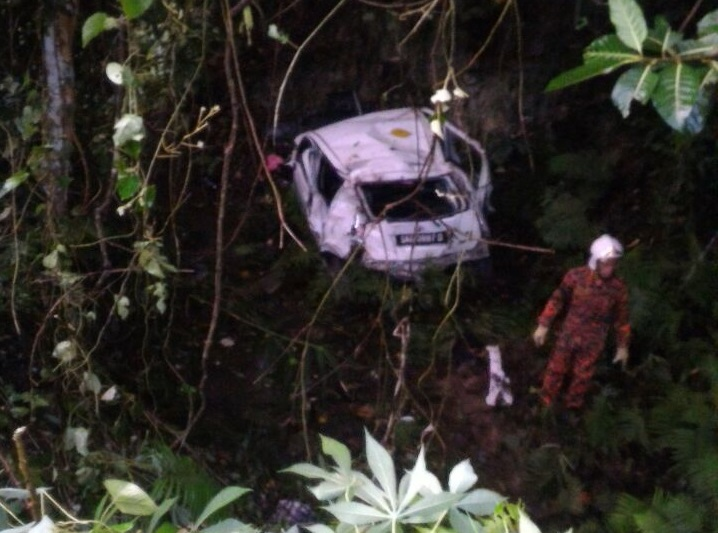 A rescuer near the ill-fated car, looking for a point to haul up the vehicle that crashed down the 20-metre deep ravine Thursday morning. - Photo credit Bomba Keningau