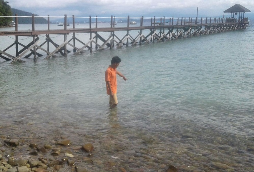 A worker at the island resort in Pulau Gaya points to the spot where the body of was found floating on Sunday.