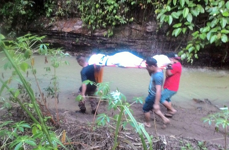 Firemen and villagers help carry the remains of of of the victims to the ambulance. - Photo credit Bomba Ranau