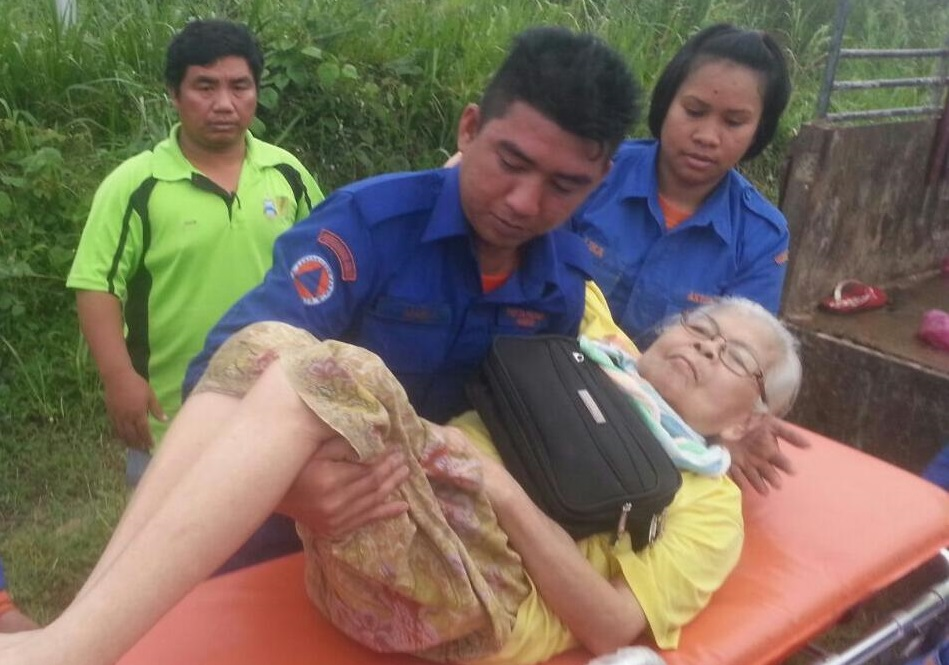 This elderly woman from Kampung Goruntung gets a helping hand from an APM Sabah personnel to be transported to the nearby evacuation centre.