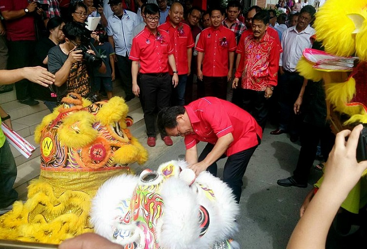 Shafie rewards a 'lion' with a mandarin orange after a lion dance performance at the Parti Warisan Sabah Chinese New Year 'open house' in Kota Kinabalu on Sunday.