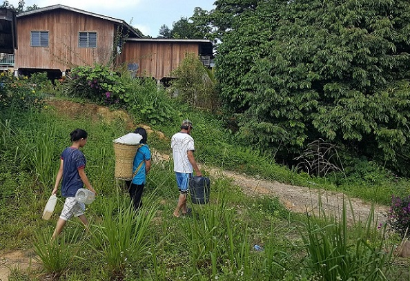 Residents of Kg Katud on their way to collect water, once upon a time.